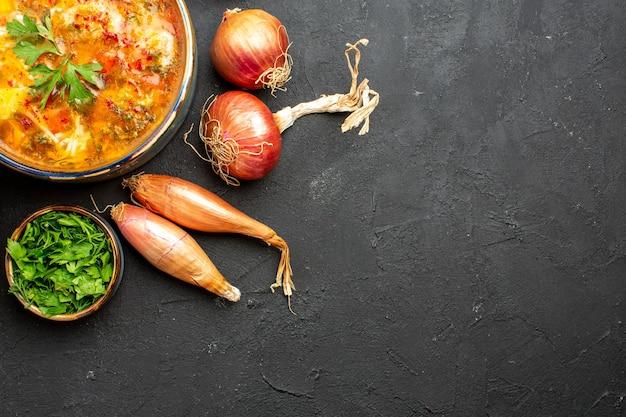 Вид сверху вкусного мясного супа с нарезанными овощами на сером пространстве