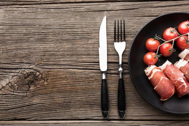 Вид сверху вкусное мясо с помидорами на столе