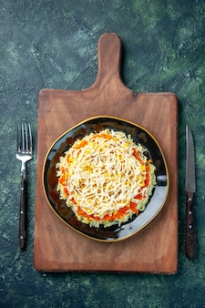 Vista dall'alto deliziosa insalata di mimosa all'interno del piatto su sfondo blu scuro