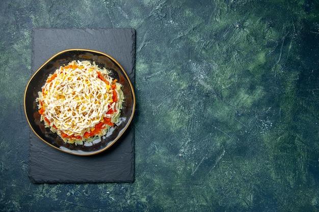 Вид сверху вкусный салат с мимозой внутри тарелки на темно-синем фоне