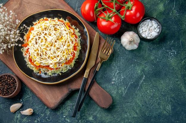 Vista dall'alto deliziosa insalata di mimosa all'interno del piatto con pomodori rossi su sfondo blu scuro