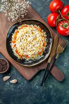 紺色の背景に赤いトマトとプレート内のおいしいミモザサラダの上面図