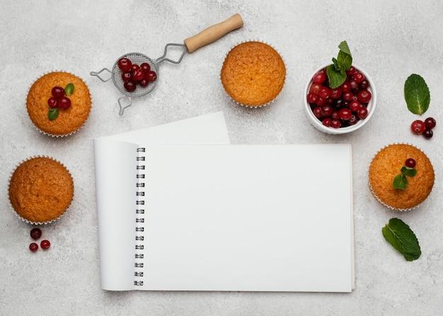 Vista dall'alto di deliziosi muffin con notebook e frutti di bosco