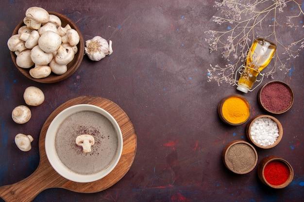 Vista dall'alto deliziosa zuppa di funghi con diversi condimenti sulla scrivania scura