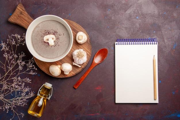 暗い机の上に新鮮なキノコと油を使ったトップビューのおいしいキノコのスープ