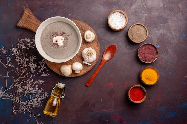 暗い机の上に新鮮なキノコと調味料を添えたトップビューのおいしいキノコのスープ