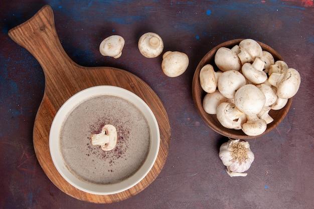 暗い机の上にキノコとトップビューのおいしいキノコのスープ