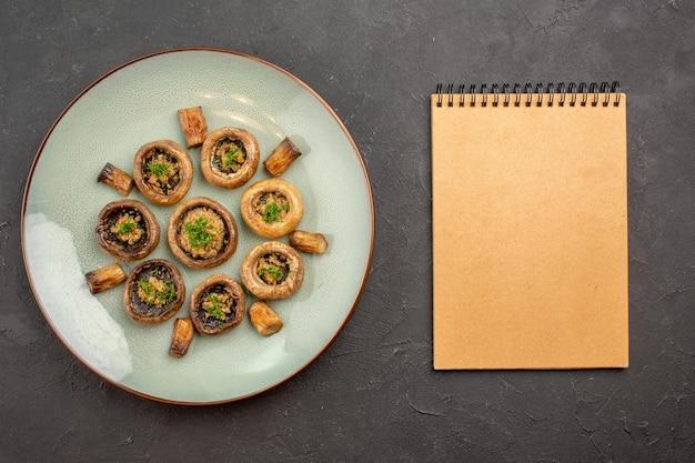 Vista dall'alto delizioso pasto di funghi cucinato con verdure su un piatto di superficie scura cena che cucina funghi
