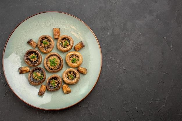 Vista dall'alto delizioso pasto di funghi cucinato con verdure all'interno del piatto sulla superficie scura piatto cena cucina selvatica matura