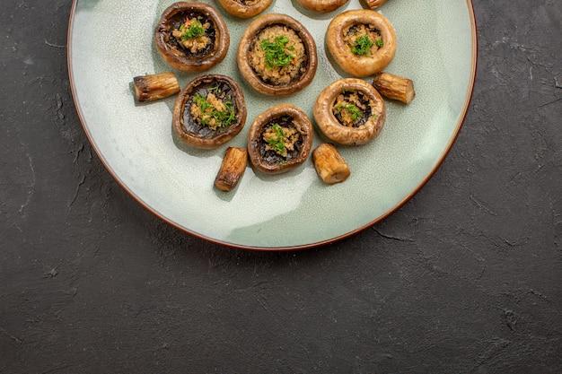 平面図おいしいキノコの食事は、暗い机の上のプレートの内側の緑で調理されています皿の夕食熟した食事は野生で調理されています