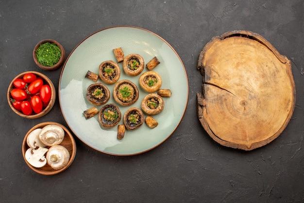 上面図暗い表面の皿に新鮮な緑とトマトを使ったおいしいキノコの食事夕食の食事調理のキノコ