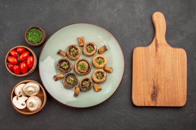 Vista dall'alto delizioso pasto a base di funghi con verdure fresche e pomodori su un piatto da scrivania scuro cena che cucina funghi