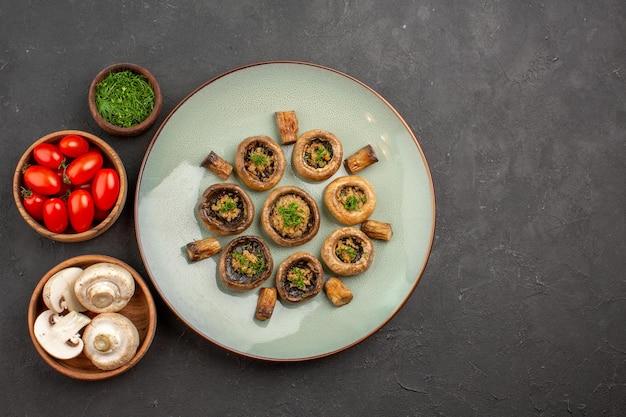Vista dall'alto delizioso pasto a base di funghi con verdure fresche e pomodori sulla superficie scura del piatto per la cena che cucina il fungo
