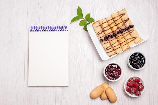 Vista dall'alto deliziosi rotoli di pancake con marmellata e biscotti su sfondo bianco biscotto biscotto marmellata marmellata