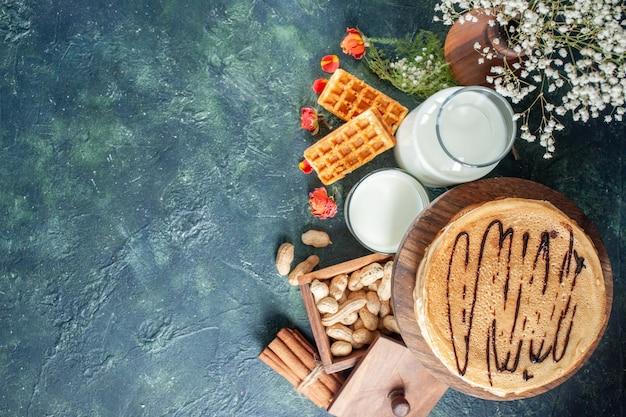 진한 파란색 표면에 신선한 우유와 견과류를 넣은 맛있는 팬케이크
