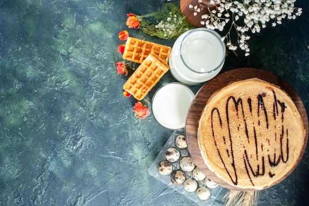 진한 파란색 표면에 신선한 우유가 있는 맛있는 팬케이크