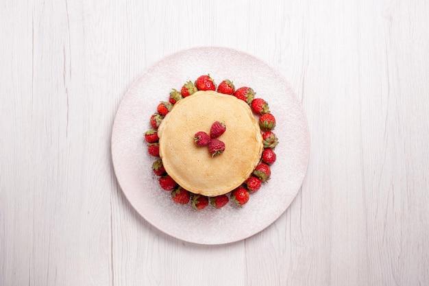 上面図白い背景に新鮮な赤いイチゴとおいしいパンケーキフルーツケーキベリーパイ甘いビスケット砂糖
