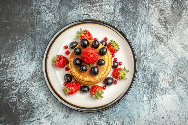 Vista dall'alto deliziose frittelle con frutta e bacche sul dessert di frutta torta superficie scura