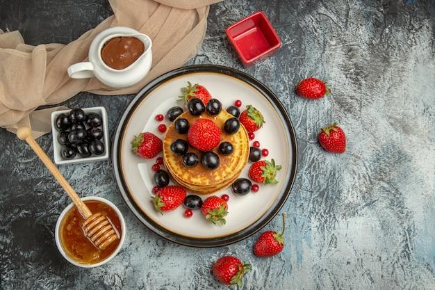 Vista dall'alto deliziose frittelle con frutta e miele sulla torta di frutta dolce superficie leggera