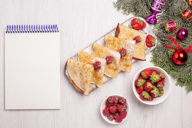 上面図白い背景の上の果物とおいしいパンケーキ甘いケーキデザートフルーツティーパンケーキ