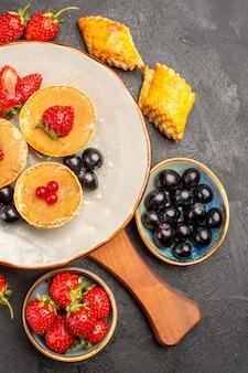 暗い机の上の果物とおいしいパンケーキの上面図パイフルーツケーキ甘い