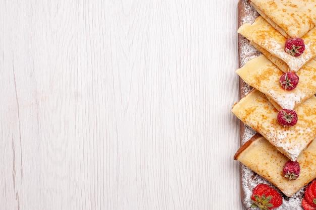 上面図白い机の上にフルーツとおいしいパンケーキ甘いデザートフルーツパンケーキシュガー