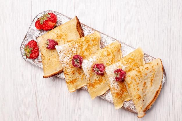 上面図白い背景の上の果物とおいしいパンケーキ甘いケーキデザートフルーツお茶のパンケーキ