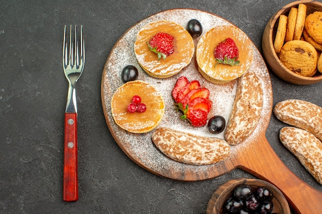 Vista dall'alto deliziose frittelle con frutta e torte dolci sul dolce da dessert torta piano scuro
