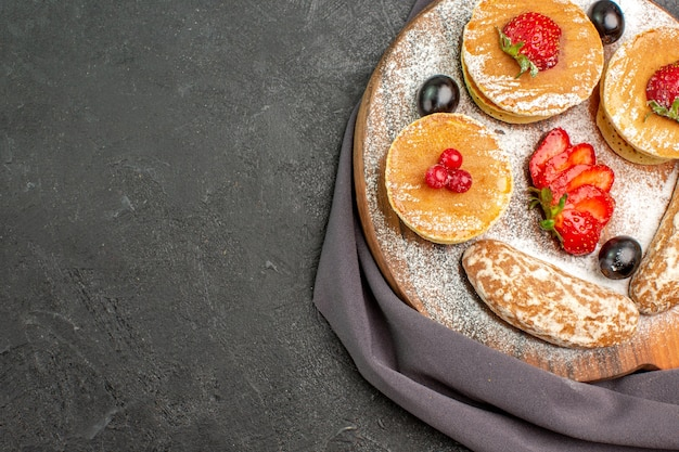 Vista dall'alto deliziose frittelle con frutta e torte dolci sulla superficie scura torta dolce da dessert