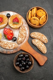 Top view delicious pancakes with fruits and sweet cakes on dark surface cakes dessert sweet
