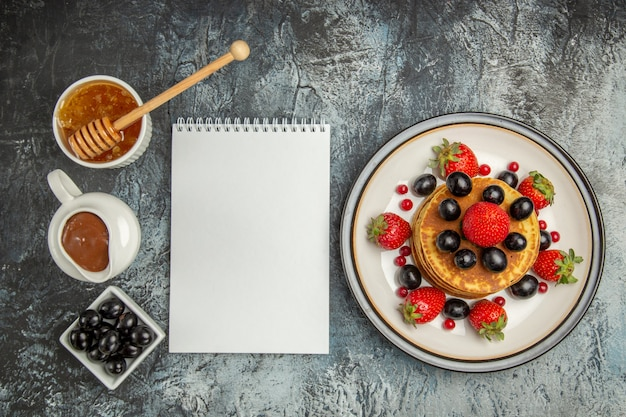 ライトフロアのフルーツケーキスウィートに蜂蜜とフルーツのトップビューおいしいパンケーキ