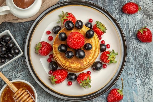 軽い表面の甘いフルーツケーキに蜂蜜とフルーツを添えたトップビューのおいしいパンケーキ