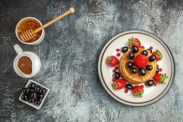 Vista dall'alto deliziose frittelle con miele e frutta sulla torta di frutta leggera scrivania dolce