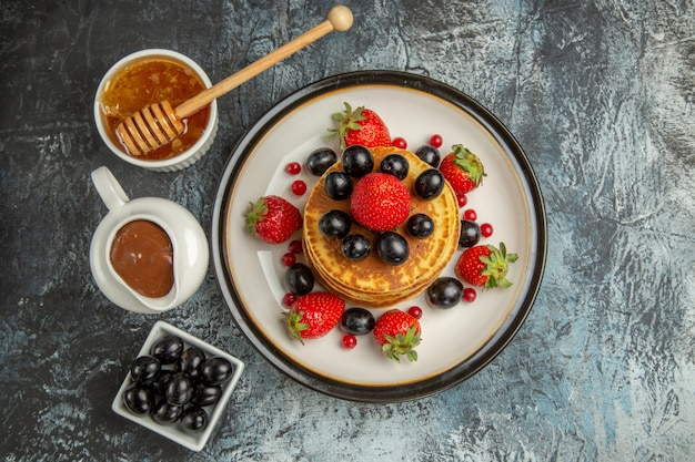 Vista dall'alto deliziose frittelle con miele e frutta su frutta dolce torta superficie leggera