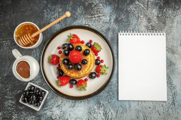 Vista dall'alto deliziose frittelle con miele e frutta sulla torta di frutta superficie leggera dolce