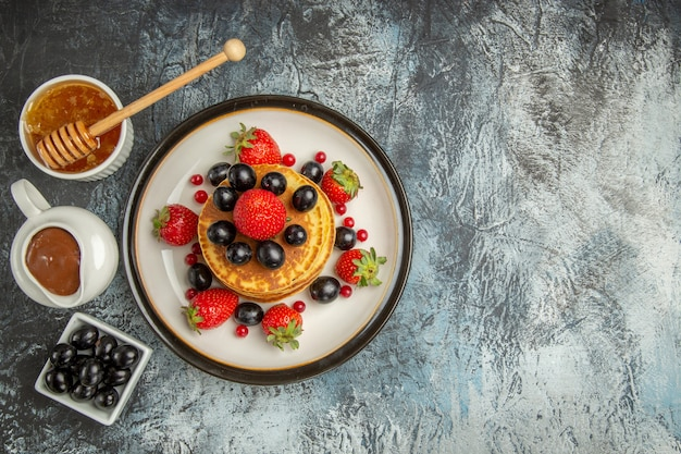 Top view delicious pancakes with honey and fruits on light surface fruit cake sweet