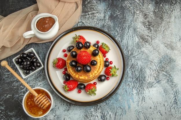 Vista dall'alto deliziose frittelle con miele e frutta sulla torta di frutta dolce superficie leggera