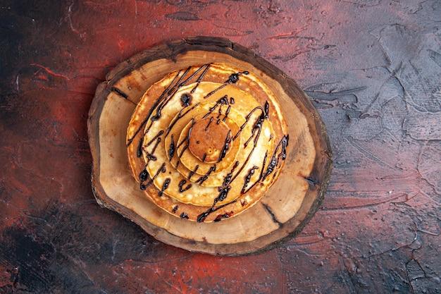 暗い表面にアイシングをしたトップビューのおいしいパンケーキ