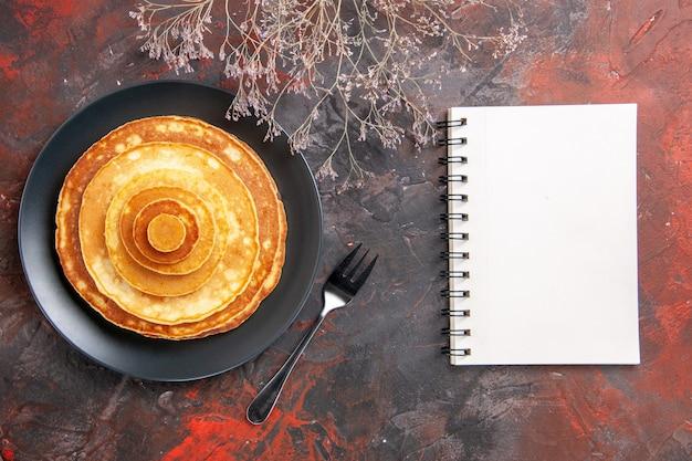 Vista dall'alto su deliziosi pancake con il taccuino