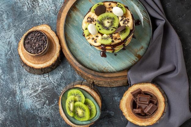 Vista dall'alto deliziose frittelle con frutta a fette e cioccolato su superficie grigio scuro torta dolce colazione zucchero frutta dessert
