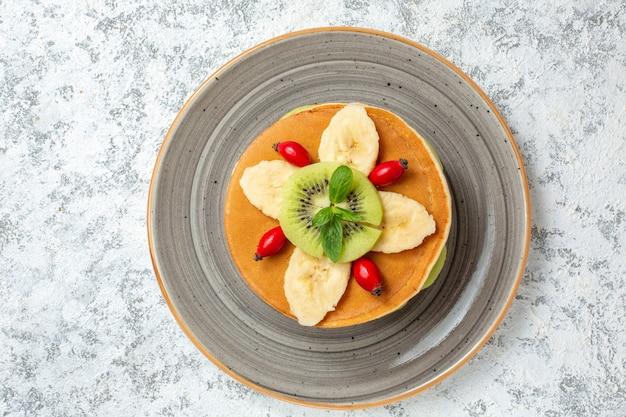 Vista dall'alto deliziose frittelle con frutta a fette all'interno del piatto su superficie bianca frutta dolce dessert torta di zucchero colore colazione