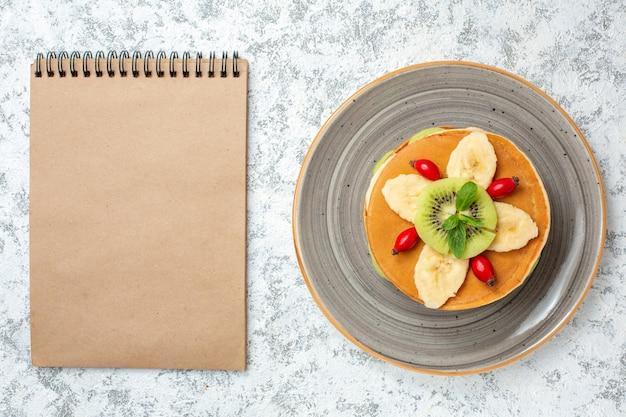Vista dall'alto deliziose frittelle con frutta a fette all'interno del piatto su superficie bianca dolce dessert torta di zucchero colore colazione - copia