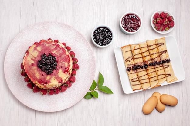 흰색 책상 파이 비스킷 달콤한 과일 케이크 베리에 딸기와 젤리와 상위 뷰 맛있는 팬케이크