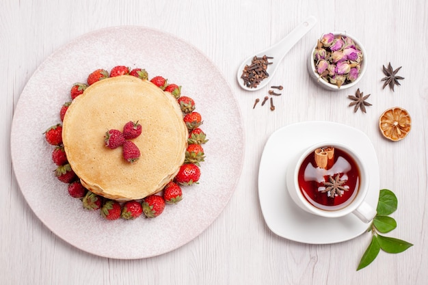 Top view delicious pancakes with strawberries and cup of tea on white background fruit pie cake biscuit sweet berry