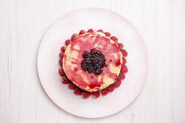 Vista dall'alto deliziose frittelle con fragole e gelatina su sfondo bianco torta di frutta biscotto dolce bacca