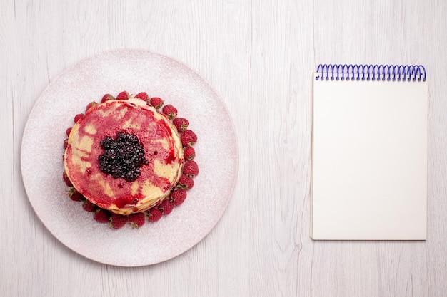 Vista dall'alto deliziose frittelle con fragole e gelatina su sfondo bianco frutta torta torta biscotto dolce bacca