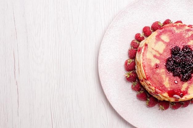 Vista dall'alto deliziose frittelle con fragole e gelatina su scrivania bianca torta torta biscotto frutti di bosco dolci