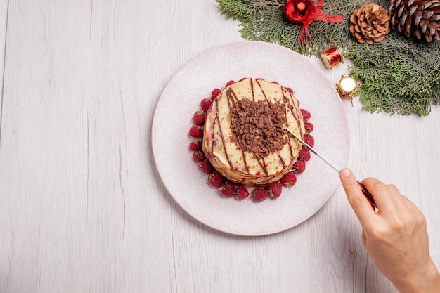 上面図白い机の上にイチゴとおいしいパンケーキパイフルーツビスケット甘いベリーケーキ