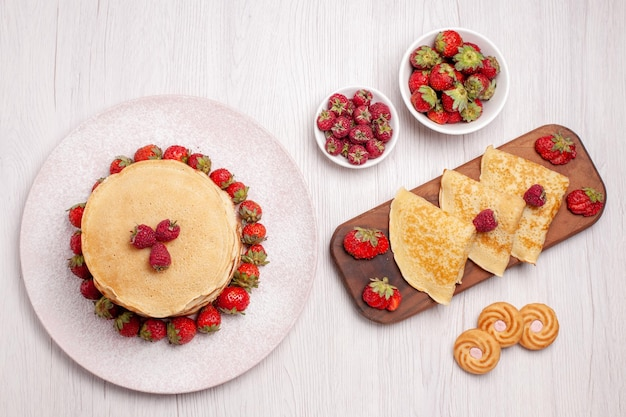 Top view delicious pancakes with strawberries on white background fruit pie cake biscuit sweet berry
