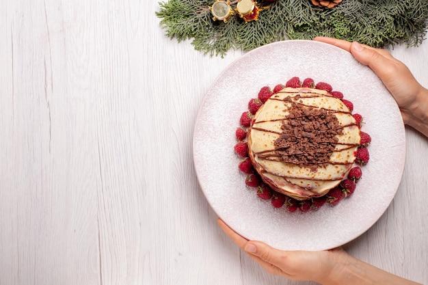 Vista dall'alto deliziose frittelle con fragole su torta bianca torta di frutta biscotto torta di bacche